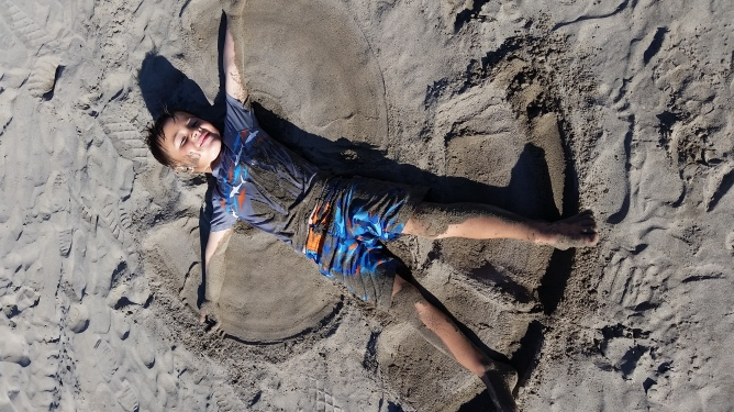 Finley makes sand angels and doesn't mind the sand in all crevices!