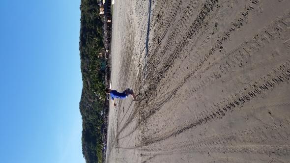 Elliott jumping along the uber-long beach at Stone Island